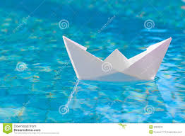 White paper boat floating in the water Stock Photo