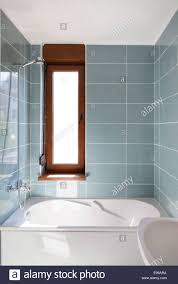 Vertical Shot of light bathtub in a bathroom with window Stock ...