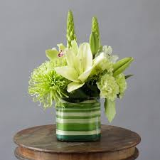 a cube vase lined with ti leaf ribbon and filled with lilies