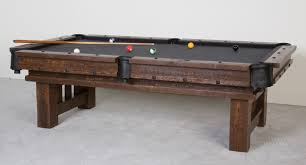 shabby brown wooden pool dining table with black counter top also two brown wooden legs placed