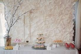 the secret garden themed baby shower dessert table featuring a stunning giant white paper flower backdrop