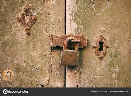 locked door closed old rusty padlock on a distressed wooden door stock photo