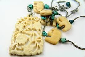 carved ivory cartouche pendant and elephants