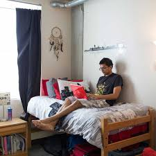 male using laptop in bed in dorm room