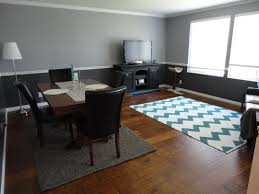 interior rectangle grey rug under rectangle dark brown wooden dining table connected by four black