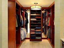small walk in closet design with mirror and modern chandelier and racks