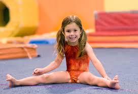floor gymnastics splits. Direct Eye Contact Froma 4 Year Old Girl In Orange Leotard As She Practices  A Straddle Floor Gymnastics Splits