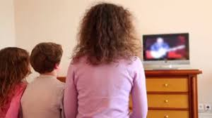 kids watching tv at night. mother with kids boy and little girl sit watch tv watching at night