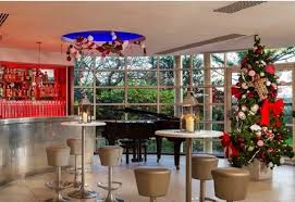 Kensington Roof Gardens Christmas Party W8, Large open windows with light  pouring through Christmas tree