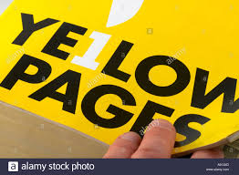 flicking through the yellow pages telephone directory stock image