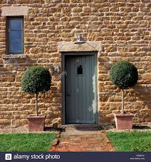 clipped bay trees in pots on either side of painted front door in small stone house