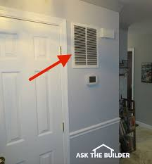 the red arrow points to a large wall mounted hvac return air vent the furnace or air handler is probably on the other side of the wall behind that door