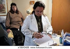 Doctor Reading Chart Doctor Reading A Womans Medical Chart Stock Photograph