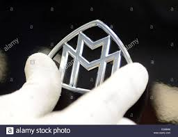 A staff members attaches the emblem of Mercedes' luxury car model ...