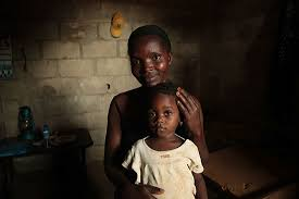 what the bible says about poverty compassion international a togolese mother her daughter in her lap sits in dark room