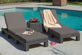 two grey rattan sun loungers set up by a pool