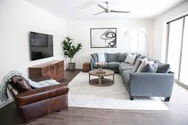 simple neutral living room design brown leather chair comfortable grey l shape sofa throw pillows accent wood round table white area rug wall entertainment