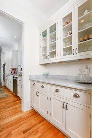 view through butlers pantry in new construction kitchen design featuring inset cabinets marble countertops