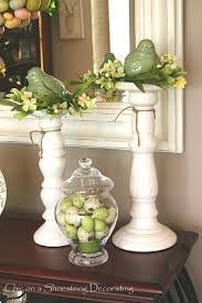 Pretty and elegant spring/Easter decorating. Top white candle holders with  a small floral or twig wreath and set ceramic birds in them.