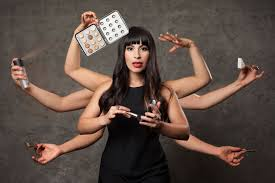heads artist in black dress with eight arms each hand holds a makeup item