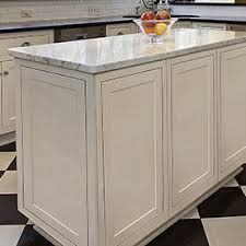Center Island In White Cabinets With Decorative Door Panels On