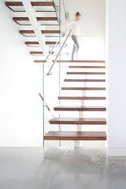 These modern stairs feature walnut treads, while brushed stainless steel  handrails are attached to glass