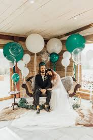 green and white giant balloon wedding decor with bride in lace wedding dress and groom in