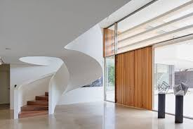 This white modern spiral staircase features a white railing and wood steps  to keep the design