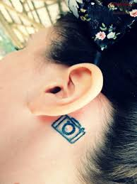 Black Little Movie Camera Tattoo On Girl Behind The Ear