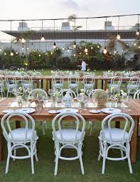 dinner area wooden table white bentwood chairs and hanging random bulbs