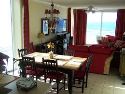 living room red fabric curtains on the hook and wooden dining set under dark red