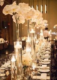 centerpieces wedding table decor tall glass vases are lush with white orchids and candles floating inside tall