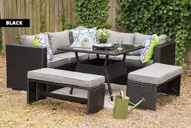 table a black rattan furniture set out on a patio with an l shaped sofa