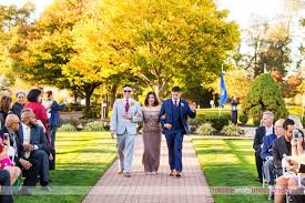 battleground country club wedding ceremony groom in blue suit waves as he walks down the aisle for outdoor wedding ceremony at