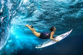 A surfer pierces a wave with her surfboard. aquatica Pinterest.