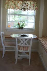 white wooden breakfast round table with straight pattern cushion on cream carpet tile as