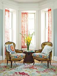 a bay window frames a pair of chairs in this seating area because of the
