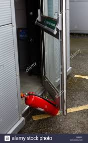 a fire extinguisher being used to prop open an office door