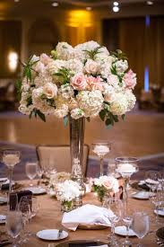 Some of the centerpieces will be tall silver vases filled with white  hydrangeas, blush peonies, white stock flowers, blush spray roses and hints  of gray ...