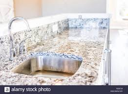 New Modern Faucet And Kitchen Sink Closeup With Granite Countertops