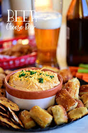 pub style beer cheese dip in bowl with pretzel and gl of beer