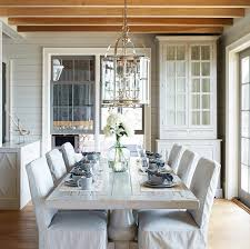 cottage dining room is filled with a whitewashed dining table lined with ticking stripe slipcovered dining chairs illuminated by two round lanterns