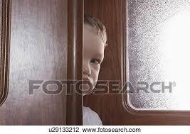 young boy ks round wooden door frame