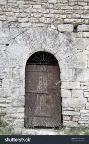 very old wooden door reinforced with nails in arched stone door frame