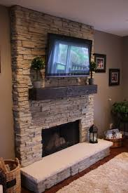 stone fire places with flat tv and fur rug