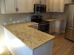 furniture white tile backsplash connected by cream granite countertops and brown wooden laminate floor
