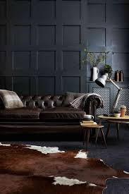a moody living room with a dark brown leather sofa and a matching animal skin rug