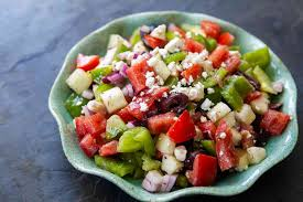 greek salad in blue bowl with feta cheese on top