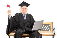 Зрелый человек в мантии градации представляя с дипломом и компьтер  Гордый созрейте студент выпускник держа диплом Стоковая Фотография