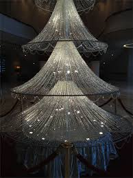 a fifteen foot crystal Christmas tree standing under a huge Swarovski  crystal chandelier.in the